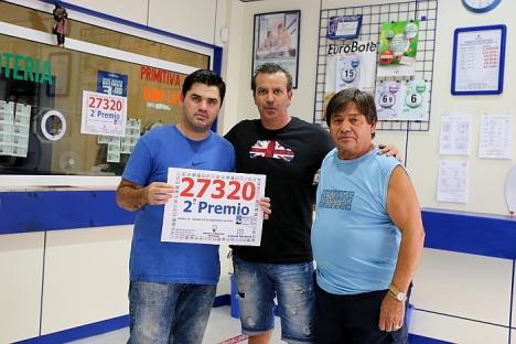 Los adminsitradores con el cartel que acedita el premio, esta mañana (Foto: Joaquín Carrión)