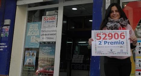Yasmina Herranz, hija e la Administradora, sostiene el cartel con el número premiado en las puertas del local