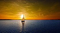 en alta mar el sol del atardecer sobre una vela