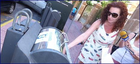La cocnejal de Medio Ambiente, Fanny Serrano, deposita un envase en un contenedor de reciclado