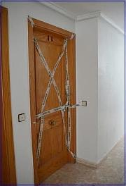 Puerta de la vivienda donde sucedieron los hechos, precintada por la Guardia Civil
