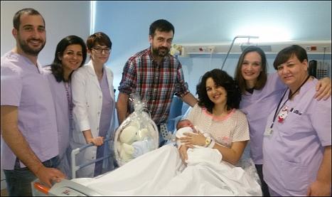 Sara, en brazos de su mamá, rodeada del equipo medico del Hospital Universitario